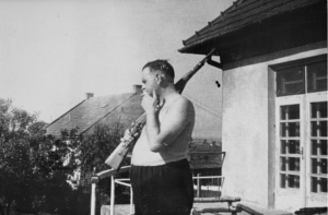 Commandant Amon Goeth stands with his rifle on the balcony of his villa in the Płaszów concentration camp